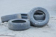 Neumáticos de goma viejos en el asfalto gris en una pila imagen de archivo
