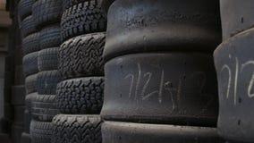 Neumáticos pulidos del coche de carreras estacados en pilas metrajes