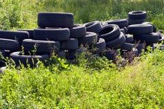 Neumáticos usados lanzados en naturaleza. Foto de archivo