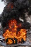 Neum?ticos de autom?vil ardiendo, llama fuerte del fuego rojo y nubes de humos negros foto de archivo