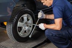Neumático de Using Rim Wrench To Tighten Car del mecánico Imágenes de archivo libres de regalías