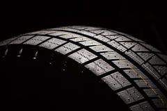 Neumático a estrenar del coche en un fondo negro. Fotos de archivo