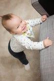 Neun Monate alte Baby, die auf ihren Füßen in einer Bemühung zu c stehen Stockfotografie