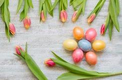 Neun rote gelbe Tulpen und sieben Ostereier auf dem hölzernen Hintergrund der Weinlese Lizenzfreies Stockbild