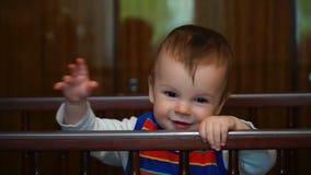 Neunmonatiger Junge der Gesamtlänge, der in der Krippe spielt stock video footage