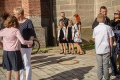 Families pose for pictures outside church. Neuoetting,Germany-June 22,2018: Families pose for pictures with their children outside the local church before Stock Photography