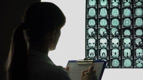 Neurólogo de sexo femenino que mira cuidadosamente la radiografía del cerebro, anotando diagnosis almacen de video