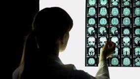 Neurochirurg die geduldige hersenenröntgenstraal bekijken, die beeld, het ziekenhuisstage richten royalty-vrije stock afbeelding