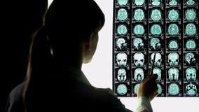 Neurochirurg die hersenenröntgenstraal analyseren, bloedvatenproblemen, ongeneeslijke ziekte royalty-vrije stock afbeelding