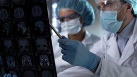 Neurocirurgião que mostra a varredura humana de MRI e que dá a explicação ao interno médico imagens de stock