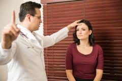 Neurolog som undersöker den kvinnliga patienten Arkivfoton