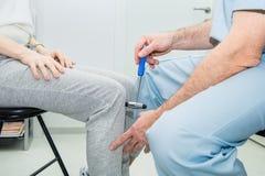 Neurologa probierczy kolanowy odruch na żeńskim pacjencie używa młot Neurologiczny fizyczny egzamin Selekcyjna ostrość, zakończen zdjęcia stock
