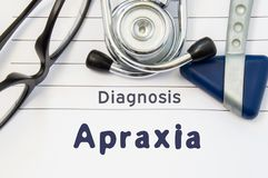 Neurological diagnosis of Apraxia. Neurological hammer, stethoscope and doctor`s glasses lie on doctor workplace on sheet of noteb. Ook, labeled with the title royalty free stock photo