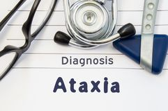 Neurological diagnosis of Ataxia. Neurological hammer, stethoscope and doctor`s glasses lie on doctor workplace on sheet of notebo. Ok, labeled with the title of Royalty Free Stock Photos