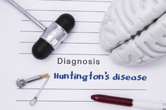 Neurological diagnosis of Huntington`s disease. Neurological hammer, human brain figure, tools for sensitivity testing are on tabl. E next to title of text stock image
