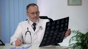 Neurologist carefully studying brain MRI, disturbed by results, making notes. Stock photo royalty free stock photos