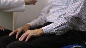 Neurologist checking arm reflex of male patient stock video footage