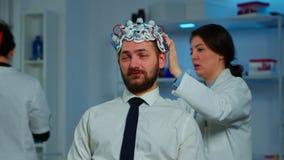 Neurologist doctor analysing brain of man using brainwave scanning headset