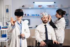 Free Neurologist Doctor Gesturing Wearing Virtual Reality Headset Stock Photo - 214881140