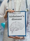 Neurologist doctor holds clipboard with Alzheimer's disease and Stock Images