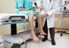 Neurologist Examining Patient's Knee With Hammer Royalty Free Stock Images