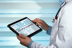 Neurologist with a sclerosis multiple diagnosis in digital medic. Doctor consulting medical record on the tablet with text sclerosis multiple in diagnostic / Royalty Free Stock Image