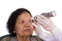 Neurologist testing reflexes of the eye of young woman Stock Photos
