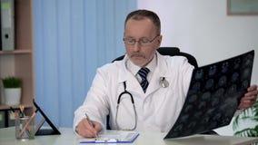 Neurologista experiente que examina com cuidado o cérebro MRI, fazendo anotações no formulário foto de stock