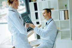 Neurologues professionnels joyeux discutant un électroencéphalogramme Photographie stock libre de droits