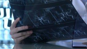 Neuroloog die geduldig x-ray beeld, het klinische onderzoek van de bloedvatenziekte kijken stock videobeelden