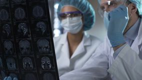 Neurosurgeon showing human MRI scan and giving explanation to medical intern. Stock footage stock footage