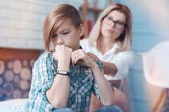 Neurotic teenage kid is not willing to answer uncomfortable questions. Cmon you can tell me everything you want. Female professional psychologist trying to calm Stock Image