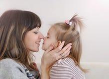 Neus aan neus moeder en haar weinig dochter die en F spelen hebben Stock Afbeelding
