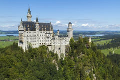 Neuschwanstein Castle amongst green trees, Bavarian Alps. Royalty Free Stock Images