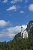 Neuschwanstein Castle amongst green trees, Bavarian Alps. Royalty Free Stock Photography