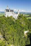 Neuschwanstein Castle amongst green trees, Bavarian Alps. Royalty Free Stock Image