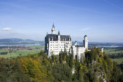 Neuschwanstein castle in autumn, Bavaria, Germany. Neuschwanstein castle in autumn on a clear sunny day with lake and city visible, Bavaria Germany Royalty Free Stock Images