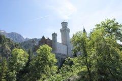 Neuschwanstein Castle behind trees from tourist scenic point Stock Photos