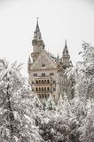 Neuschwanstein Castle with a blanket of snow in winter. Neuschwanstein near Fussen in Bavaria, Germany. The road for a walk on the Alpsee lake is surrounded by Stock Photo