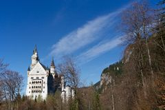 Neuschwanstein Castle in the forest. New Swanstone Castle is a nineteenth-century Romanesque Revival palace on a rugged hill above the village of Hohenschwangau royalty free stock image