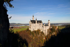 Neuschwanstein Castle in Germany. The background is Bavarian Alps region Royalty Free Stock Photo