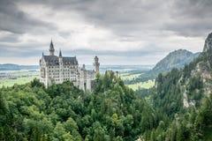 Neuschwanstein castle. Panoramic view of the Neuschwanstein castle in Bavaria with a stormy sky Stock Image