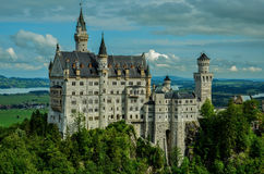 Neuschwanstein Castle. Photo shows famous castle in Germany, Neuschwanstein. Castle build on the hillside. In the background we can see lakes and river Stock Image
