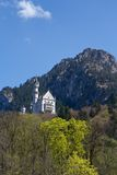 Neuschwanstein Castle in spring. New Swanstone Castle is a nineteenth-century Romanesque Revival palace on a rugged hill above the village of Hohenschwangau near stock photo