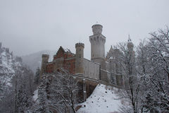 Neuschwanstein Castle in winter time between trees. Fussen. Germany. Royalty Free Stock Images