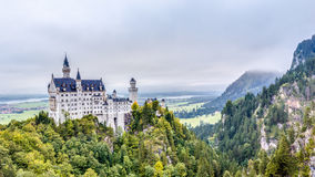 Neuschwanstein. Lovely Autumn Landscape Panorama Picture of the fairy tale castle near Munich in Bavaria, Germany in the morning hours on a foggy day Royalty Free Stock Photography