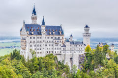 Neuschwanstein. Lovely Autumn Landscape Panorama Picture of the fairy tale castle near Munich in Bavaria, Germany in the morning hours on a foggy day Royalty Free Stock Images