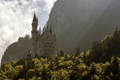 Neuschwanstein in the shadow of the great mountain Royalty Free Stock Images