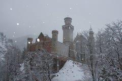 Neuschwanstein slott i vintertid mellan träd Fussen germany Royaltyfri Bild
