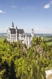 Neuschwanstein slott ovanför skogen Arkivbilder